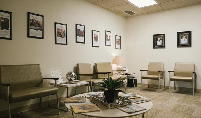 office waiting room with five chairs, two side tables, coffee table and nine pictures on the walls